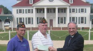 District 23 presents a check to American Village